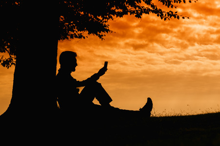 young tree: Man silhouette sitting under tree with book on cloudy day outdoor