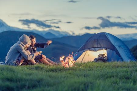 夕日山に火のキャンプ 3 人の友人 写真素材