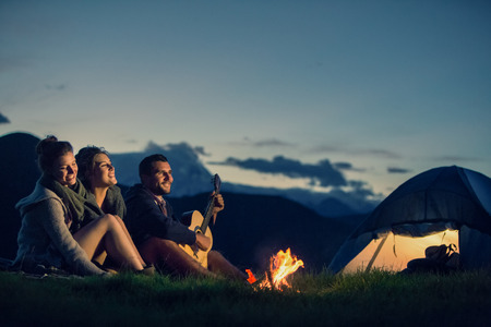 Three friends camping with fire on mountain at sunset Foto de archivo