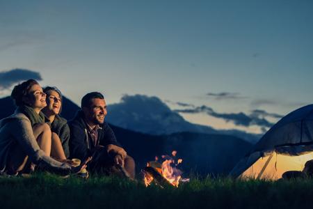 Drei Freunde mit dem Feuer auf dem Berg bei Sonnenuntergang Camping