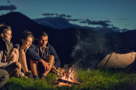 Three friends camping with fire on mountain at sunset Banco de Imagens