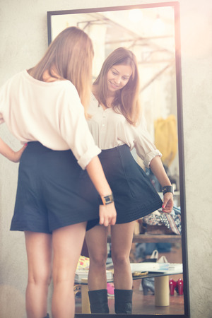 Young woman looking in the mirror try black skirt in a shop Banque d'images