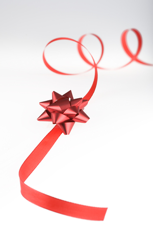 red gift wrap red ribbon with bow isolated on grey