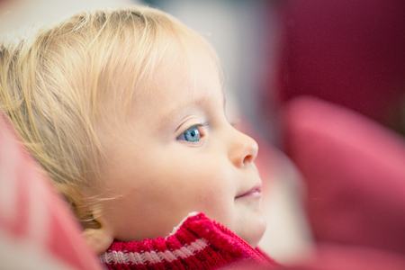 blonde yeux bleus: Little blond blue eyes girl with red sweater at home