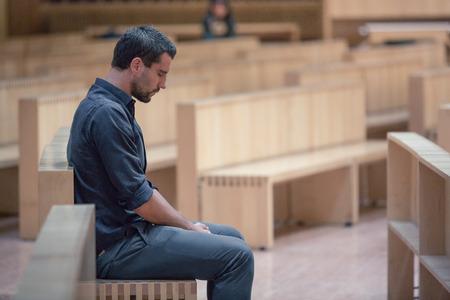 若いひげ男現代の教会で祈っている青いシャツを着て
