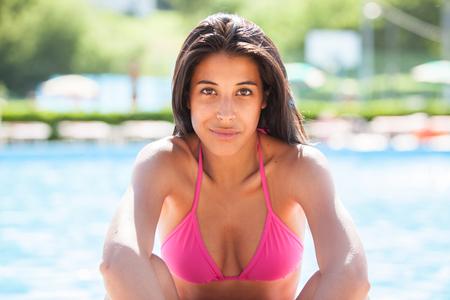 スイミング プールでのピンクのビキニの肖像画の美しい若いラティーナ女性