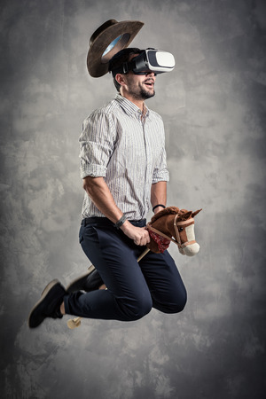 cowboy beard: young caucasian adult man enjoy experiencing immersive Virtual Reality cowboy game simulation.VR portrait concept with western horse and hat Stock Photo