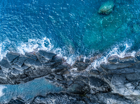 aerial overhead top view of ocean mediterranean sea waves reaching and crashing on rocky shore beach, near travel landmark destination Cinque terre National Park, Liguria, Italy. Sunny weather. Banco de Imagens