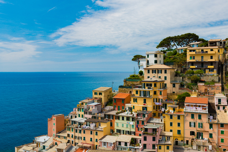 view of famous travel landmark destination Riomaggiore colorful houses, small mediterranean old sea town,Cinque terre National Park, Liguria, Italy. Summer sunny morning with clouds