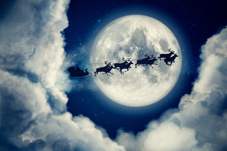 Blue xmas eve night with moon and clouds with Santa Claus sleight and reindeer silhouette flying to bring gifts and presents with text space to place or copy. Christmas present greeting post card