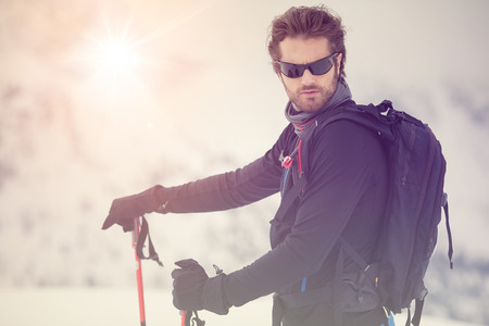 skier man detail with sunglasses. exploring snowy land walking and skiing with alpine ski. Europe Alps. Winter sunny day, snow, wide shot, warm sun flare.travelling Stock Photo