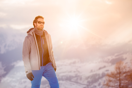 skier man detail wearing anorak jacket with sunglasses portrait. exploring snowy land walking and skiing with alpine ski. Europe Alps. Winter sunny day, snow, wide shot, warm sun flare.travelling Stock Photo