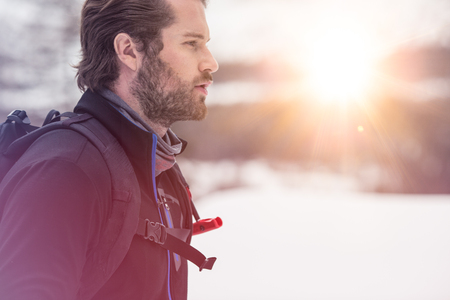 backpacker man detail wearing anorak jacket. exploring snowy land walking and skiing with alpine ski. Europe Alps. Winter sunny day, snow, wide shot, warm sun flare.travelling, side view Stock Photo