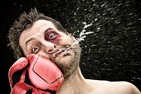 silly boxer man takes a punch in the face isolated on black.funny concept portrait Imagens - 91319214