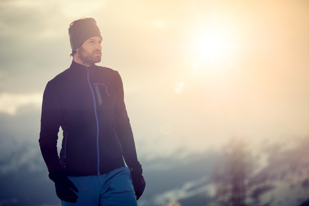 skier man detail wearing second layer jacket. exploring snowy land walking and skiing with alpine ski. Europe Alps. Winter sunny day, snow, wide shot, warm sun flare.travelling