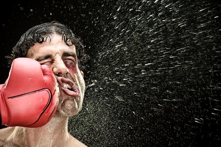dummer Boxermann macht einen Schlag im Gesicht, das auf Schwarzem lokalisiert wird Lustiges Konzeptporträt