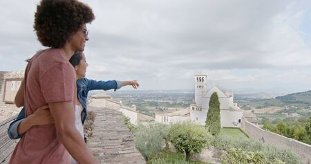 Romantic couple walking visiting happy rural town of Assisi.Back follow.Friends italian trip in Umbria.4k slow motion