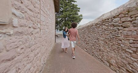 Romantic couple walking visiting happy rural town of Assisi.Back follow.Friends italian trip in Umbria.4k slow motion Stock Photo - 124982717
