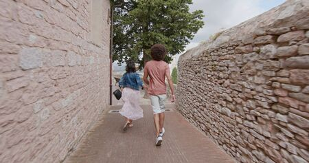 Romantic couple walking visiting happy rural town of Assisi.Back follow.Friends italian trip in Umbria.4k slow motion Stock Photo - 124982718