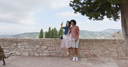 Romantic couple taking a selfie with smartphone in rural town of Assisi.approach wide shot.Friends italian trip in Umbria.4k slow motion