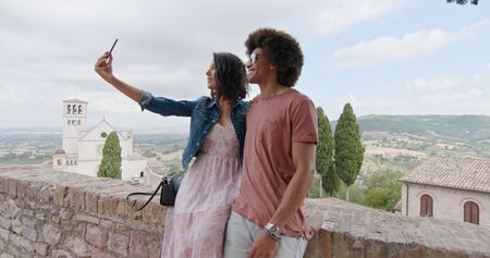 Romantic couple taking a selfie with smartphone in rural town of Assisi.Portrait medium shot.Friends italian trip in Umbria.4k slow motion