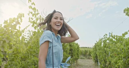 Romantic love couple, woman smiling running and walking near vineyard at sunset or sunrise.Warm sun back light.Following POV point of view.Friends italian trip in Umbria
