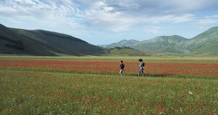 Aerial view flying above two people couple hiking or nordic walking outdoor on a trail path near flower fields in Castelluccio di Norcia.Approaching forward. Friends italian trip in Umbria.4k drone