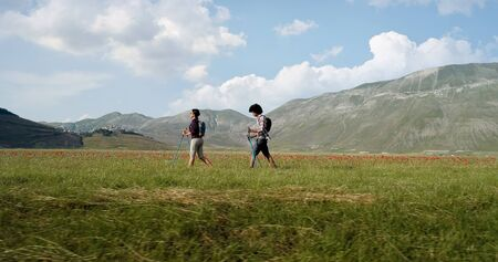 Aerial view flying above two people couple hiking or nordic walking outdoor on a trail path near flower fields in Castelluccio di Norcia. side follow. Friends italian trip in Umbria.4k drone