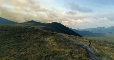 Aerial view flying above hiker man hiking or nordic walking outdoor on a trail path near Castelluccio di Norcia at sunset or sunrise.Approaching forward. Friends italian trip in Umbria.4k drone