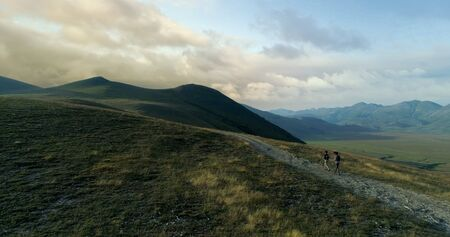 Aerial view flying above two people couple hiking or nordic walking outdoor on a trail path near Castelluccio di Norcia at sunset or sunrise.Approaching forward.Friends italian trip in Umbria.4k drone