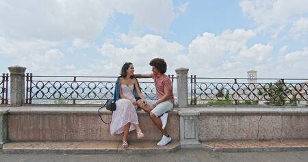 Romantic couple sitting on bench talking feeling free and happy to the main square in rural town of Assisi.back removal.Friends italian trip in Umbria.4k slow motion Stock Photo