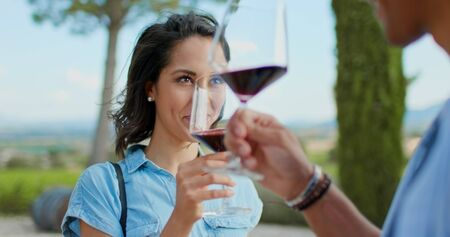 Romantic couple, woman toasting and smiling with red wine at sunset warm light. Friends italian trip in Umbria Stock Photo