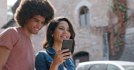 Romantic couple using smartphone to search amenities or landmarks in rural town of Assisi.Portrait medium shot.Friends italian trip in Umbria.4k slow motion Stock Photo - 124982961