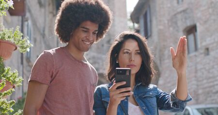 Romantic couple using smartphone to search amenities or landmarks in rural town of Assisi.Portrait medium shot.Friends italian trip in Umbria.4k slow motion Stock Photo