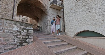 Romantic couple walking visiting rural town of Assisi.Side follow. Friends italian trip in Umbria.4k slow motion