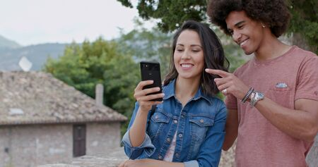 Romantic couple taking using smartphone in rural town of Assisi.Portrait medium shot.Friends italian trip in Umbria.4k slow motion Stock Photo