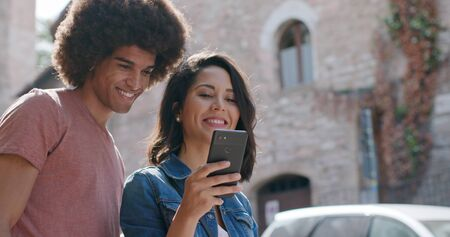 Romantic couple using smartphone to search amenities or landmarks in rural town of Assisi.Portrait medium shot.Friends italian trip in Umbria.4k slow motion Stock Photo - 124982981
