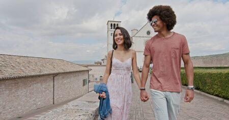 Romantic couple walking feeling free and happy to the main square in rural town of Assisi.Medium shot.Friends italian trip in Umbria.4k slow motion Stock Photo