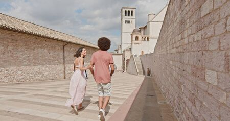 Romantic couple walking feeling free and happy to the main square in rural town of Assisi.Medium shot.Friends italian trip in Umbria.4k slow motion Stock Photo - 124982984