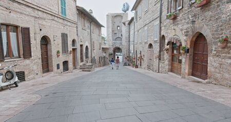 Romantic couple walking visiting rural town of Assisi.Back follow.Friends italian trip in Umbria.4k slow motion