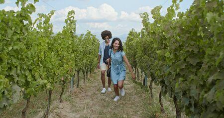 Romantic love couple walking and playful running thru green vineyards. Front follow wide shot.Friends italian trip in Umbria.4k slow motion Stok Fotoğraf