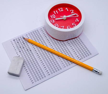Answers sheet with yellow sharp pencil, clock and rubber isolated on white background. Top view of them. Take the exam timely concept.