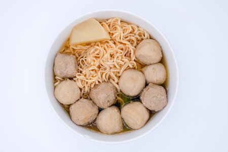 Close up and top view: Instant noodles with meat balls in white bowl and isolated on white background. Spicy tasty, street food. Stock Photo