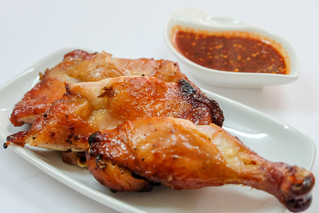 Top view and close up: juicy grilled chicken wing on white plate and spicy Thai Style sauce isolated on white background. Recommend menu with papaya salad(SOM TUM) famous and popular food. Stock Photo