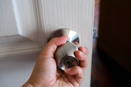 Close up of a hand holding a doorknob, opening or closing a door.