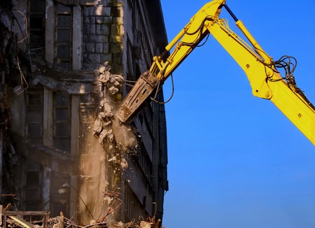Building demolition with yellow excavator