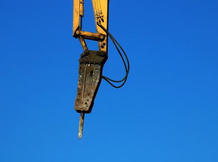 Hydraulic hammer on blue sky