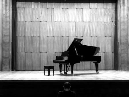 El hombre mira el piano de cola negro en el escenario, blanco y negro