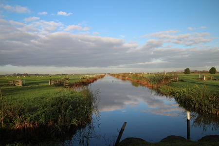 dark clouds reflecting in the water at the dike or Donderdam Stock Photo