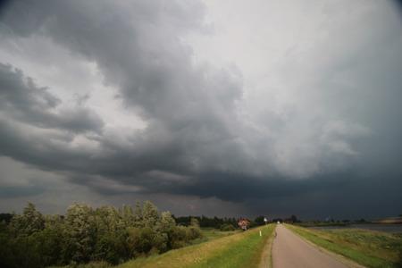 Dark storm clouds above river and dike Hollandse IJssel in Moordrecht  the Netherlands.